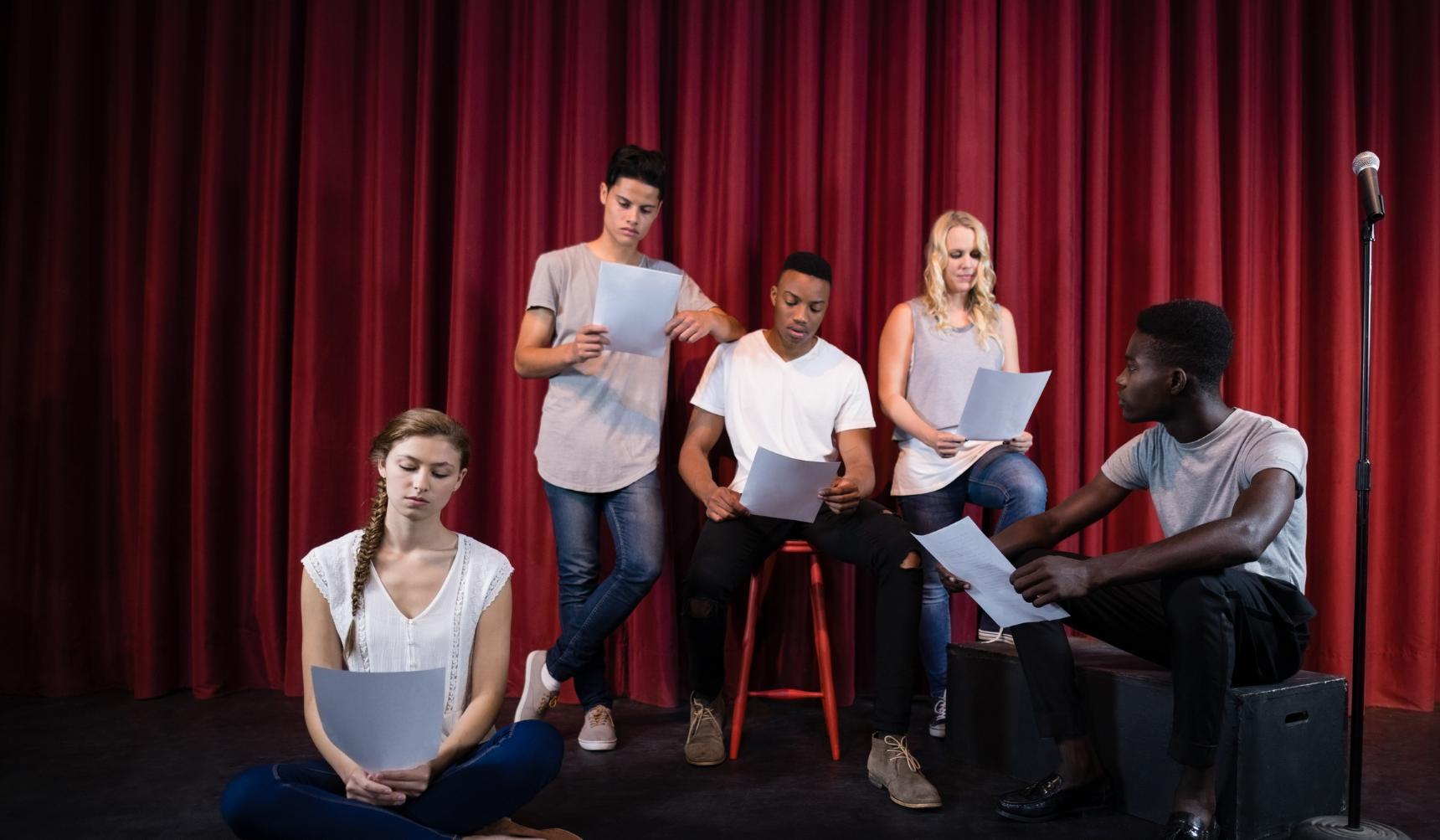 Drama pupils on stage reading scripts