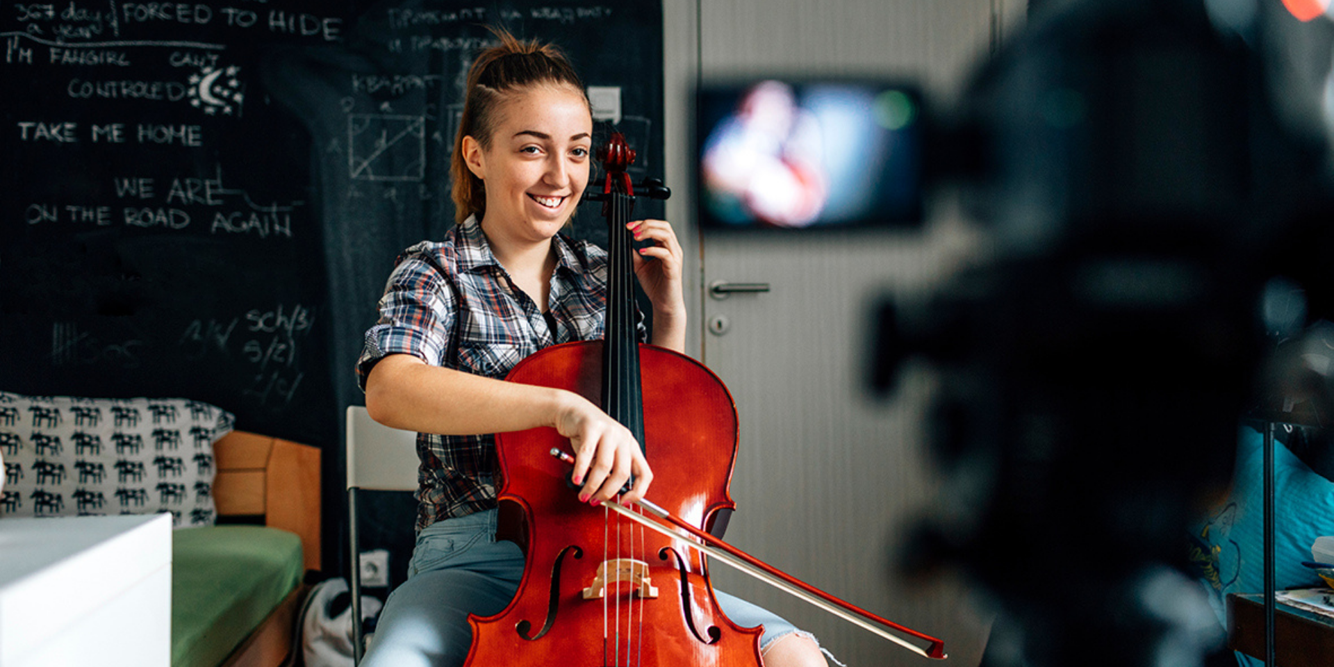 Girl playing cello facing a video camera