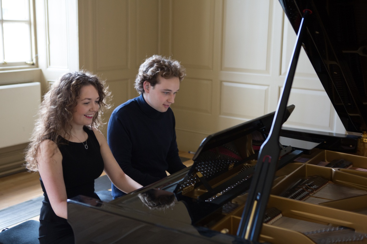 Male and female duetting on a piano