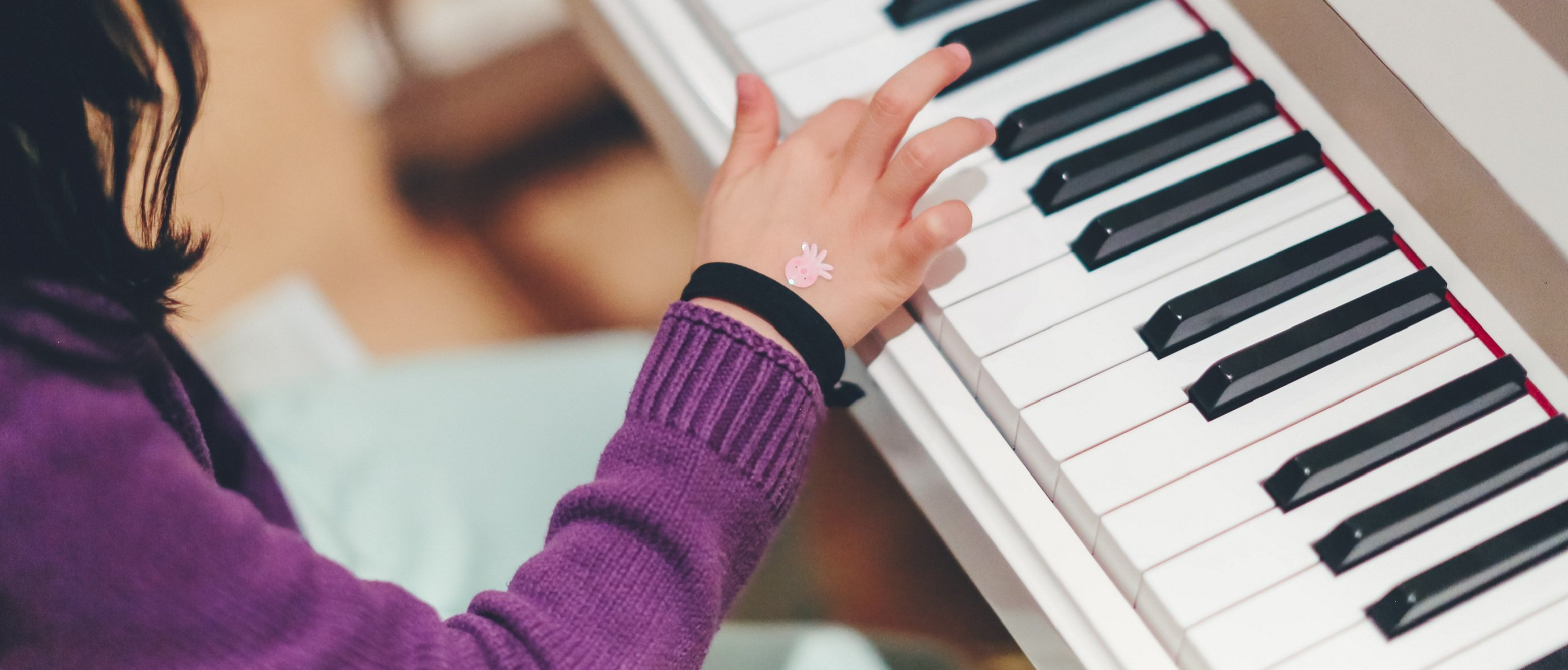 A child's right arm and hand as they press a key on a white piano. They wear a purple jumper, a black wristband and a pink octopus sticker on their hand.